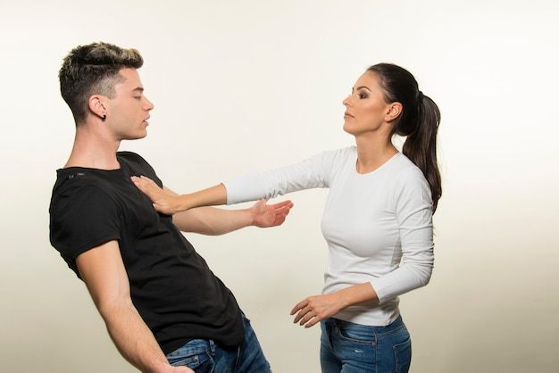 若いカップルが孤立した白い背景を主張