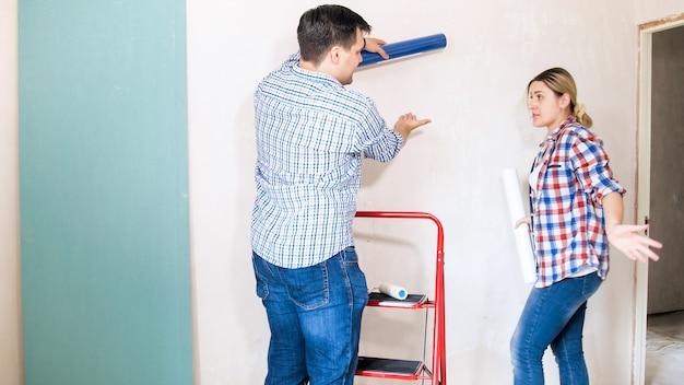 새 집에서 혁신을 위해 최고의 월페이퍼를 선택하는 동안 논쟁하는 젊은 부부.
