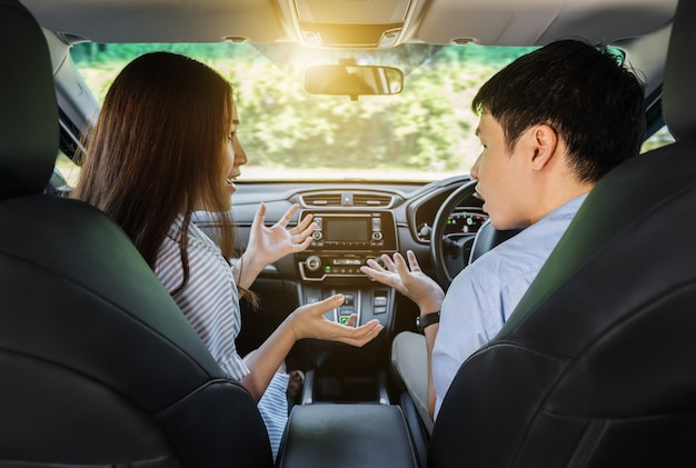 Молодая пара спорит за рулем автомобиля