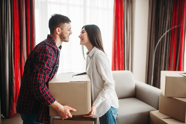 Young couple arrange carton boxes on a room, moving to new house. relocation to apartment with packaging