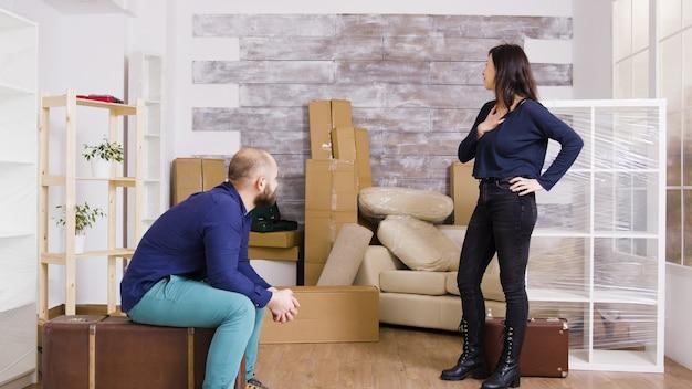 新しいアパートにスーツケースを持って到着する若いカップル。バックグラウンドで段ボール箱。