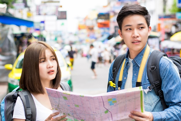 Young couple asian tourist backpacker getting lost and looking for direction