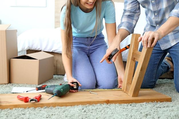 Молодая пара, собирающая мебель дома
