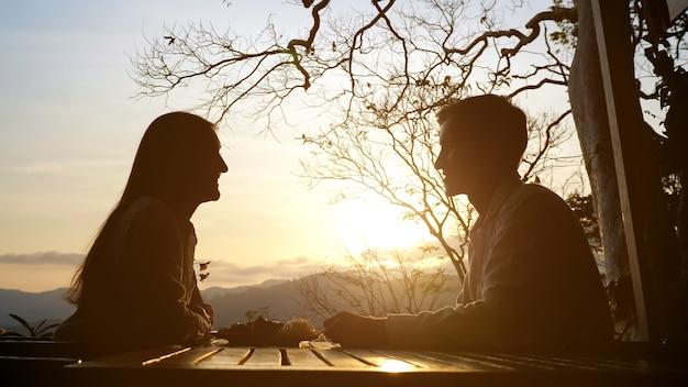 Молодая пара за столиком в кафе на фоне красивого заката.