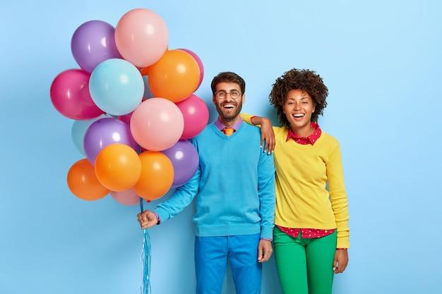 風船でポーズをとるパーティーで若いカップル