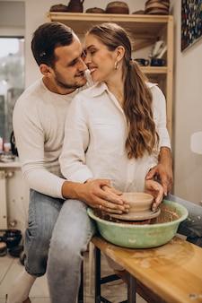 Молодая пара вместе на уроке гончарного дела