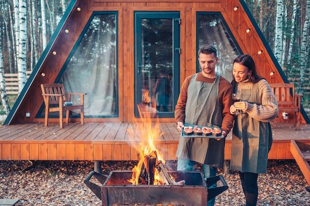 秋の暖かい日のグリルとリラックスで若いカップル