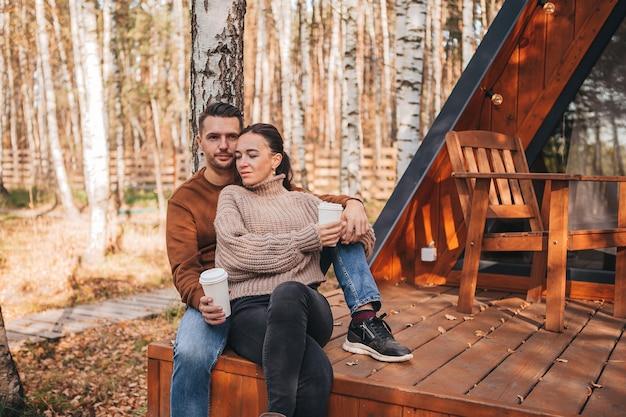 彼らの家のテラスで秋の暖かい日に若いカップル