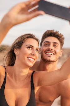 Selfieを取ってビーチで若いカップル
