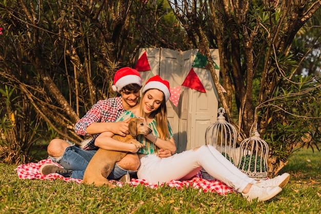 彼らのペットとクリスマスの時期に若いカップル