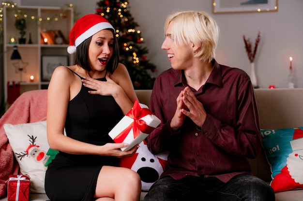 Молодая пара дома на рождество в шляпе санта-клауса сидит