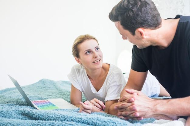 노트북 컴퓨터와 함께 침대에 집에서 젊은 부부