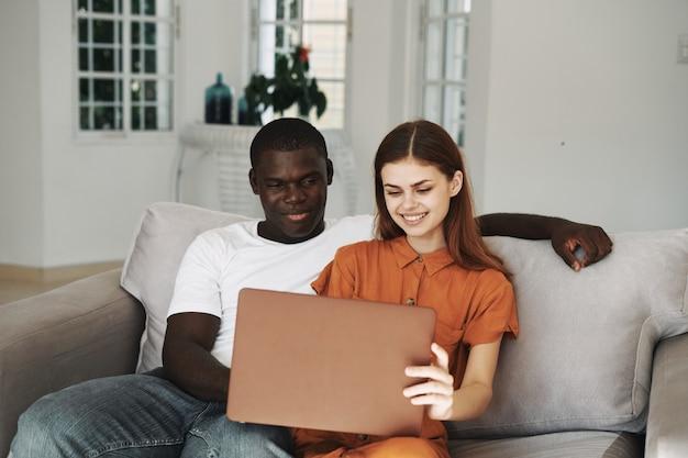 노트북 앞 소파에 집에서 젊은 부부