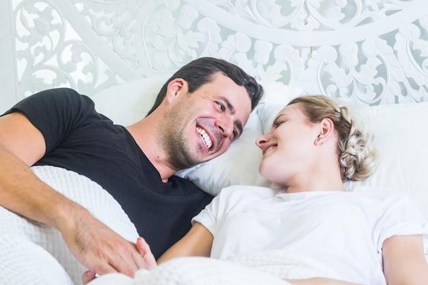 自宅やホテルのベッドでお互いを見て、愛と情熱を持って近くにいる若いカップル
