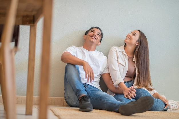家で若いカップルが床に座って空を見上げて笑っている-愛と関係の概念と住宅ローンと一緒に新しい生活-異人種間の男の子と女の子