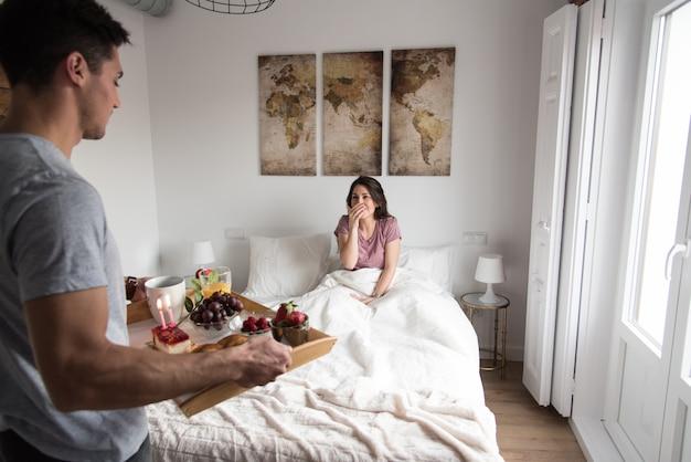 若いカップルが自宅のベッドで朝食と朝食