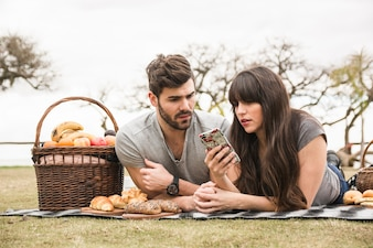 Young couple at picnic looking at mobile phone