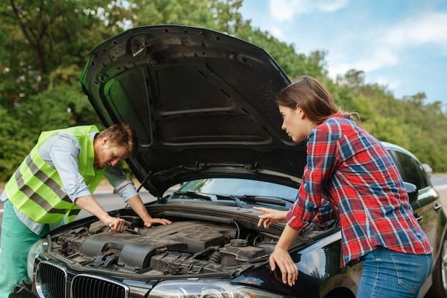 Молодая пара у открытого капота на дороге, поломка автомобиля. разбитый автомобиль или аварийная авария с автомобилем, неисправность двигателя на шоссе