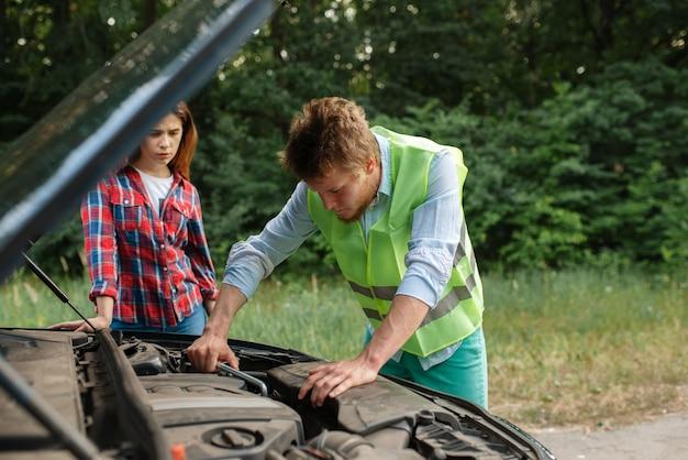 Молодая пара у открытого капота на дороге, поломка автомобиля.