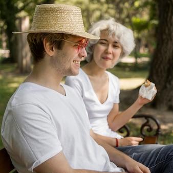 ハンバーガーを食べる公園で若いカップル