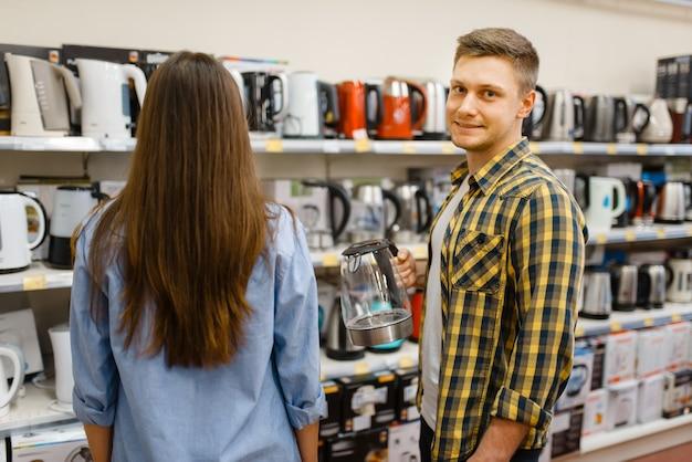전자 제품 매장에서 전기 주전자와 선반에 젊은 부부. 남자와 여자는 시장에서 가전 제품을 구입