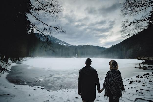 自然の湖の近くに立って戻って若いカップル。