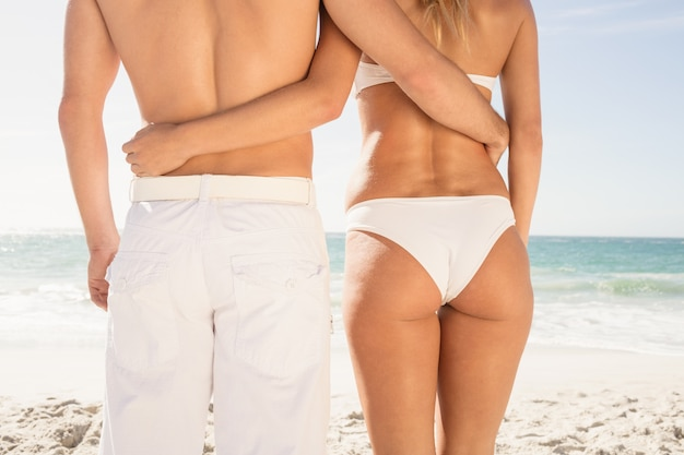 Young couple in beachwear embracing