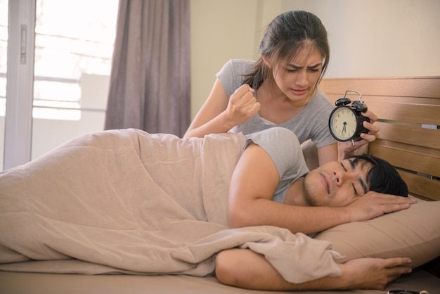 Young couple in bed, alarm clock annoying his wife who wake up.