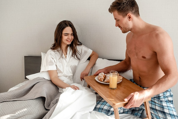 Young couple in the bed. beautiful man is holding the table with delicious breakfast for his sweetheart