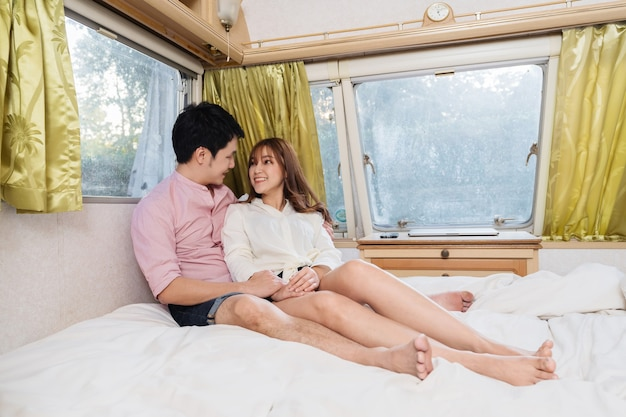Young couple on bed of a camper rv van motorhome