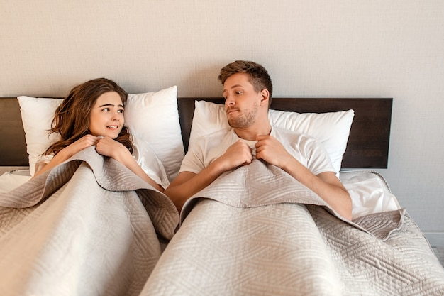 Young couple in the bed. fear of sex, shy woman and man hidding under blanket before intimacy