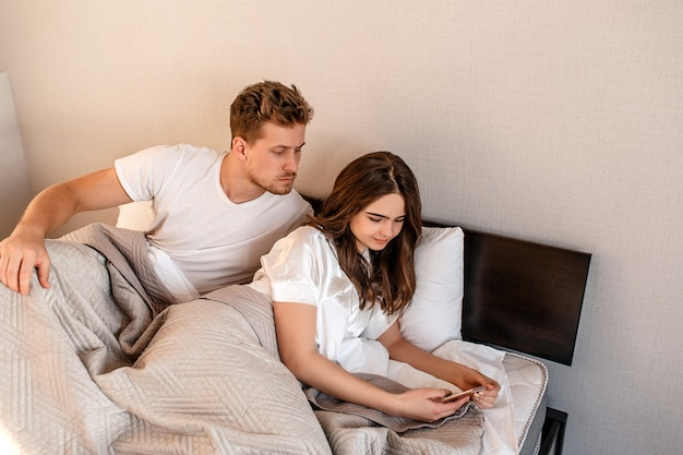 Young couple in the bed. serious man is spying his girlfriend's phone, relationships problems