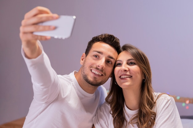 Giovani coppie a letto che prendono selfie