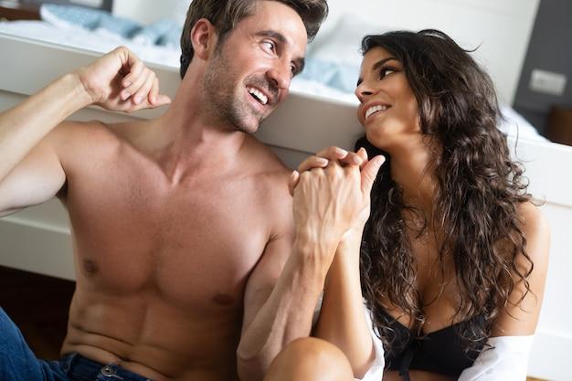 寝室で親密な若いカップル。寝室で恋をする官能的な恋人たち。