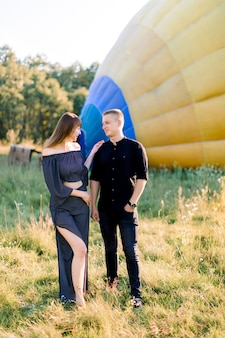 Young couple in black clothes, hugging and holding hands, while standing in summer field in front of colorful air balloon, preparing for the flight