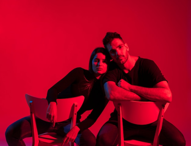 Young couple in black clothes sitting on chairs