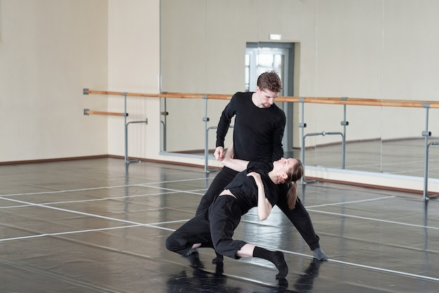 Young couple in black pants and t-shirts training one of dance exercise during lesson in large modern studio of dancing