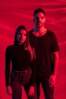 Young couple in black standing on red background