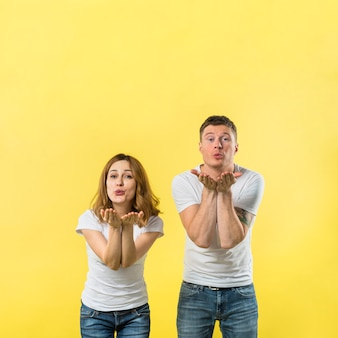 Young couple blowing her kisses against yellow background