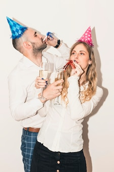 Young couple blowing in penny whistles