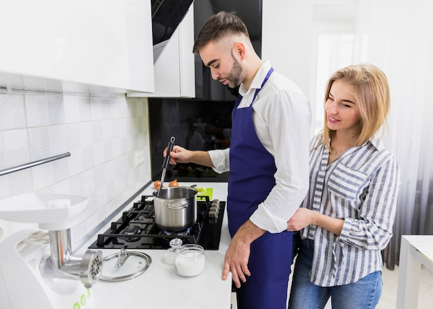 Young couple boiling water in pot on stove