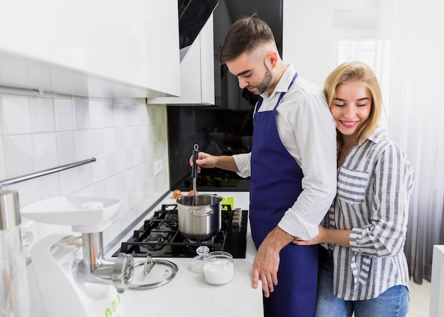 Young couple boiling water in pot