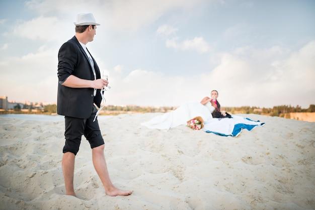 若いカップルの新郎新婦は、日当たりの良い暖かい夏の夜に海沿いの砂浜で結婚式を祝います