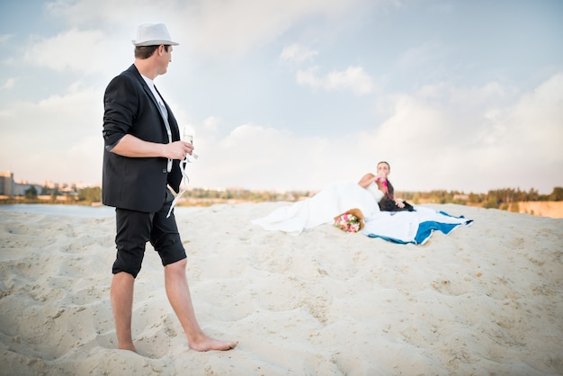 Young couple bride and groom celebrate their wedding on a sandy beach by the sea on a sunny warm summer evening