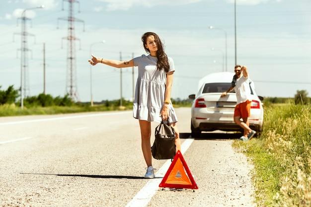 La giovane coppia ha rotto la macchina mentre era in viaggio per riposarsi. stanno cercando di fermare altri conducenti e chiedere aiuto o fare l'autostop. relazione, guai per strada, vacanze.