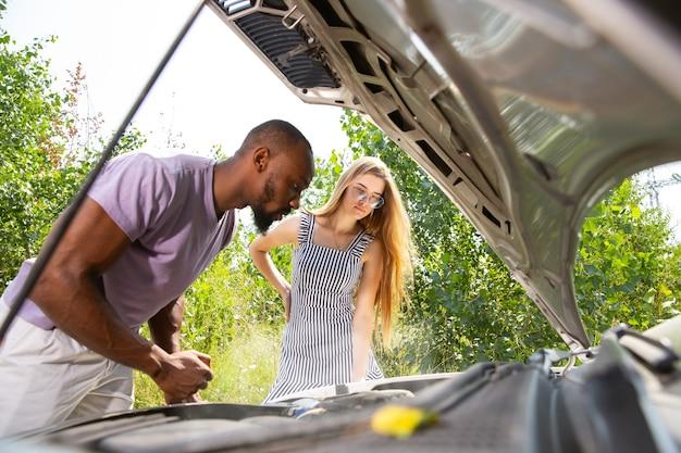 若いカップルが旅行中に車を壊した