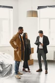 若いカップルが新しい家を買う。アジアの女性とアフリカの男性。新居で書類にサイン。