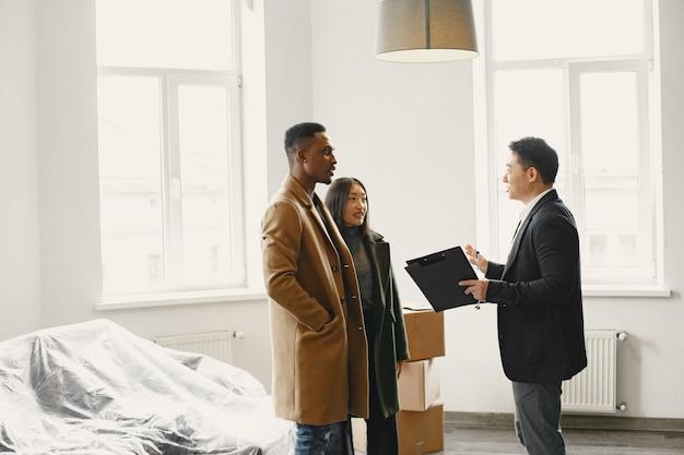 새 집을 구입하는 젊은 부부. 아시아 여자와 아프리카 남자. 새 집에서 문서에 서명합니다.