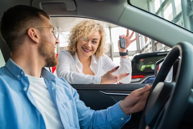 Молодая пара покупает новую машину