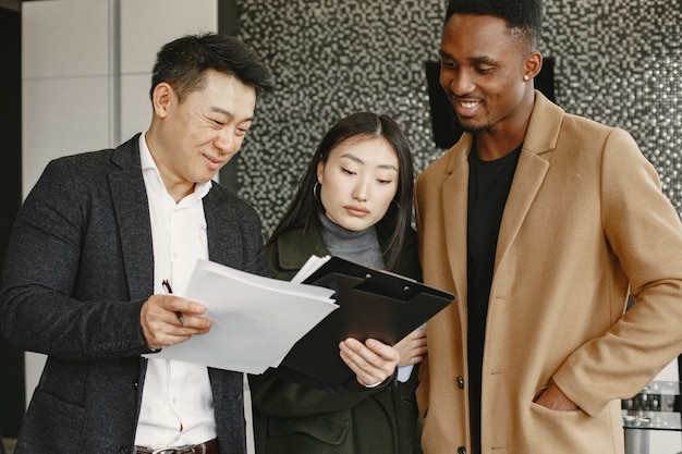 Young couple buying a new house. asian woman and african man. signing documents at new home.